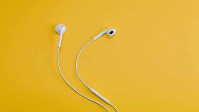 Apple Kopfhörer vor eine gelben Hintergrund