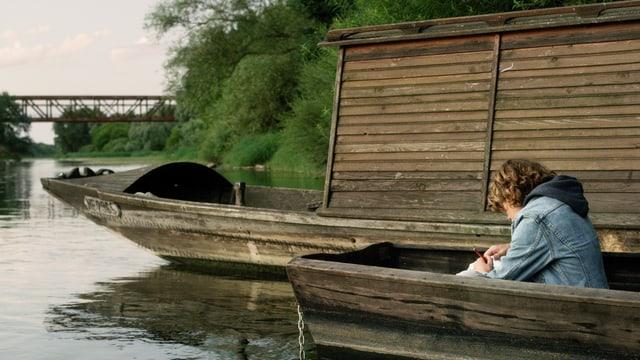 Ein Knabe sitzt auf einem Fluss in einem Holzboot.
