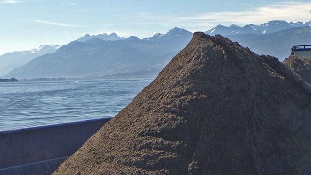 Sandberg vor Alpen-Panorama.