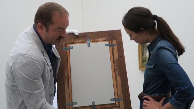 Ein Mann hält am linken Bildrand ein Gemälde, von dem man die Rückseite sieht, während eine Frau das Gemälde begutachtet.