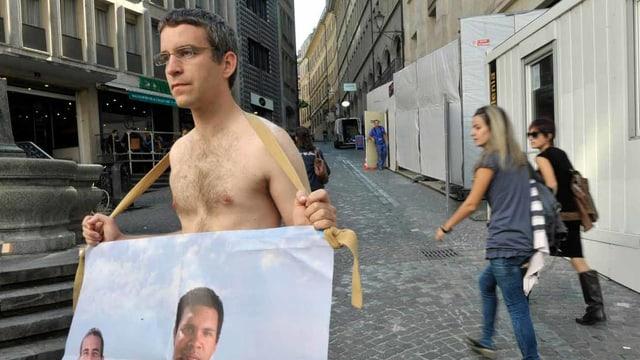Ein nackter Mann hält ein Plakat.