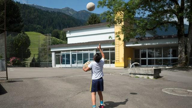 Junge spielt mit Ball auf dem Platz vor dem Zentrum