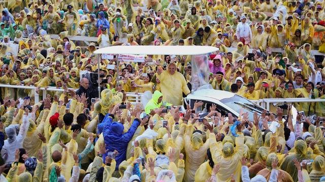 Papst im Regenschutz im Papamobil.