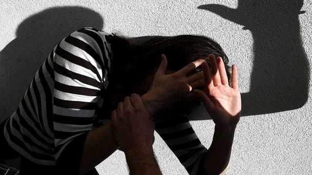 Eine Frau wird an die Wand gedrängt und hält sich die Hände vors Gesicht.