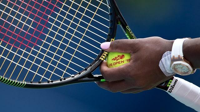 Tennisracket ist im Hintergrund.Im Vordergrund ist Serena WIlliams Hand mit Tennisball. Nägel sind rosa gefärbt.