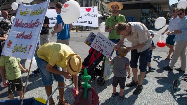 Babs ed uffants durant ina manifestaziun per il congedi da paternitad.