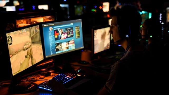Mann vor Computerbildschirm in dunkler Umgebung