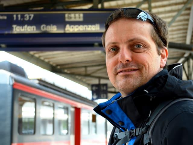 """Ein Mann steht an einem Bahnhof. Im Hintergrund die Anzeigetafel mit der Aufschrift """"Appenzell""""."""