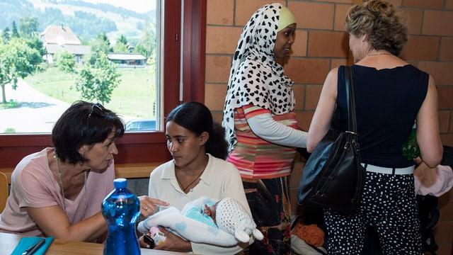 Bundesrätin Doris Leuthard und Bundesrätin  Evelyne Widmer-Schlumpf sprechen mit Asylbewerberinnen.
