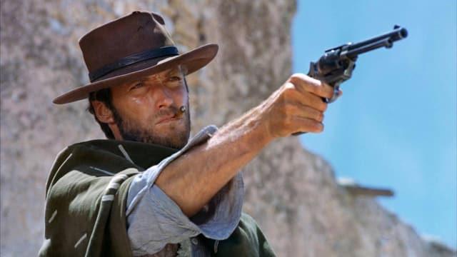 EIn Mann mit Cowboyhut, Poncho und Cigarillo zielt mit einer Pistole.