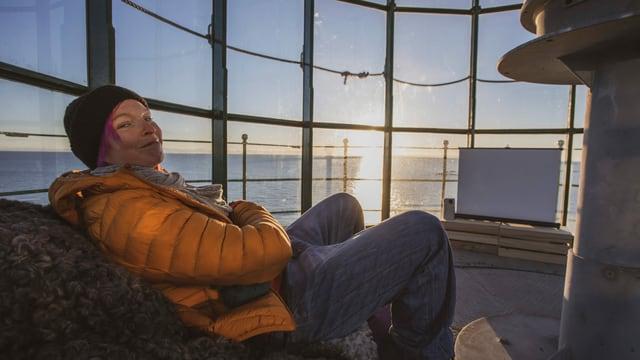 Frau mit oranger Jacke sitzt im Leuchtturm vor Sonnenuntergang