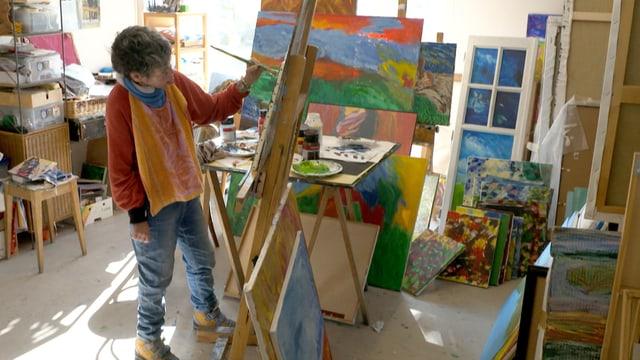 Eine Frau steht vor einer Leinwand mit einer abstrakten Landschaft in grellen Farben.
