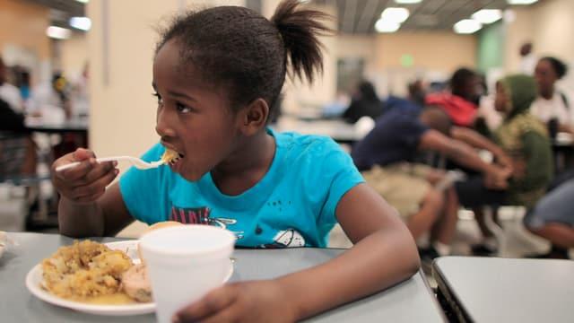 Ein Mädchen isst in einer sozialen Einrichtung.