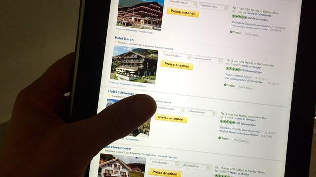 Eine Hand hält ein Tablet, es zeigt die Website von Tripadvisor.
