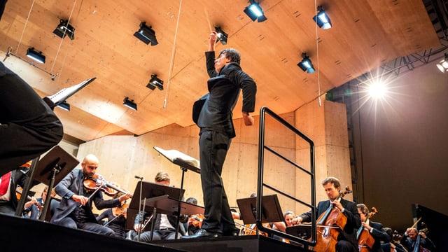 Die Bühne aus der Froschperspektive: Der Dirigent in Aktion, vor ihm das Orchester.