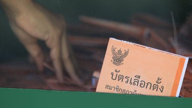 Hand fischt Wahlzettel aus einer Urne.