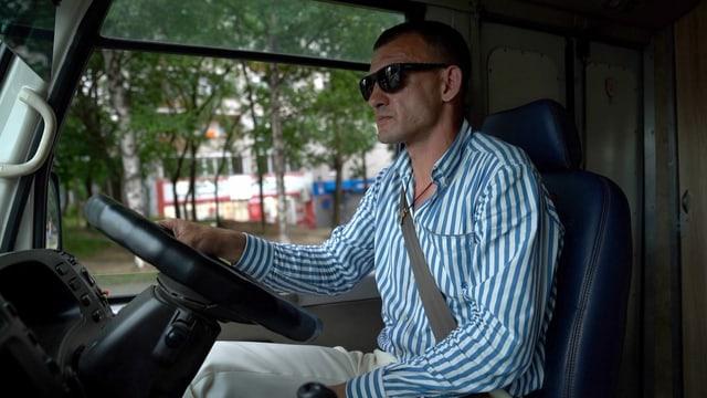 Mann in Streifenhemd am Steuer von Kleinbus.