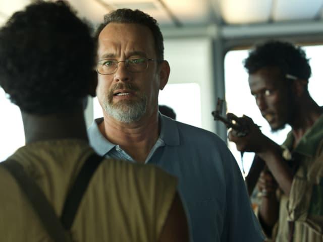 Filmszene: Tom Hanks als Schiffskapitän zwischen zwei Piraten. Einer richtet sein Gewehr auf ihn.