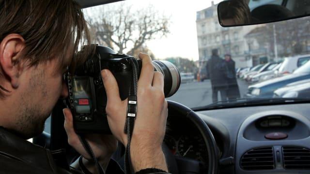 Ein Mann sitzt in einem Auto und fotografiertheimlich ein Paar.