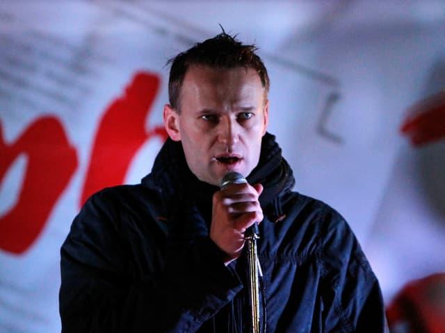 Mann spricht auf einer Bühne