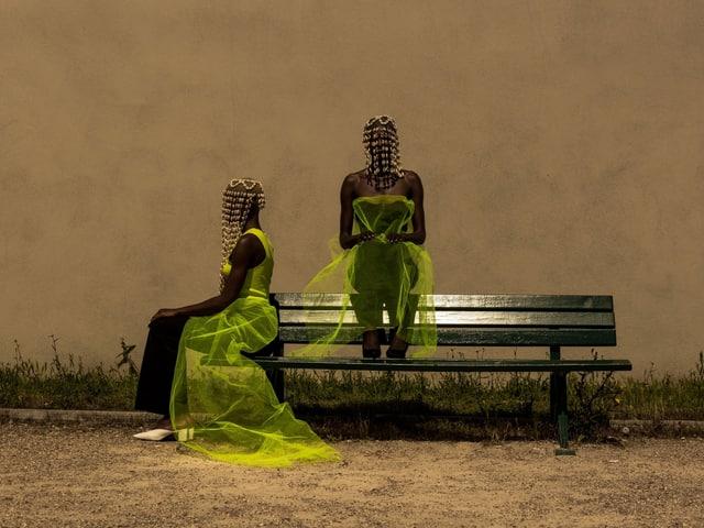 Zwei schwarze Frauen in neongelbem Tüll und mit Holzperlenschmuck sitzen auf einer Bank.