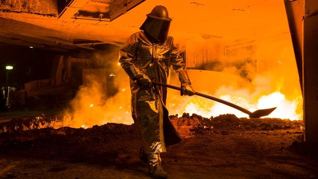 Stahlarbeiter in Schutzanzug mit Schaufel vor einem glühenden Hochofen.