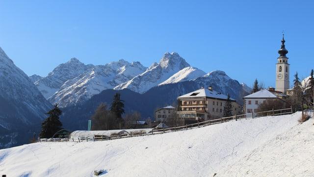 Kirche in Scuol vor schneebedeckten Bergen.