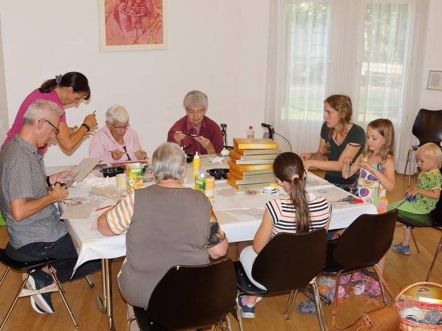 An einem Tisch voller Bastelmaterialien sitzen Menschen verschiedenen Alters.