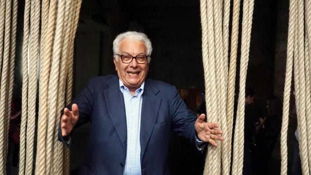 Ein älterer Mann tritt durch einen Vorhang aus dicken Seilen.