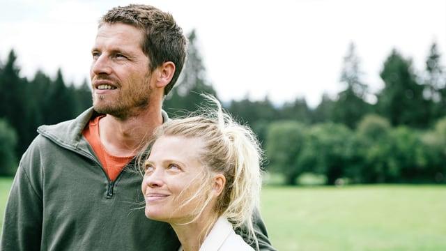 EIn Mann und eine Frau stehen in einer grünen Landschaft und schauen gespannt auf etwas, das sich ausserhalb des Bildes befindet.
