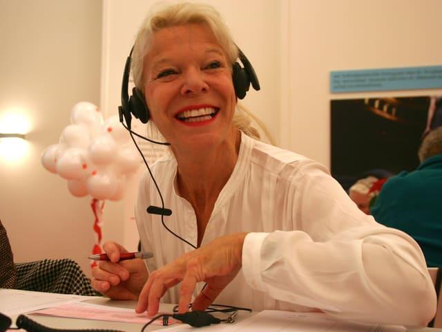 Eine lachende Frau mit Kopfhörer sitzt am Tisch, lacht, nimmt Spenden entgegen.