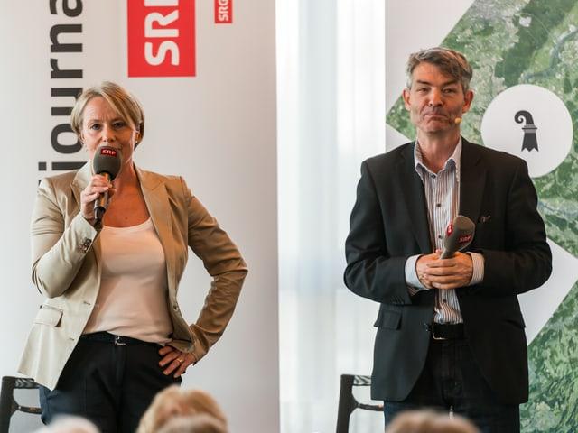 Schneider mit Mikrofon und Kohler vor Plakaten.