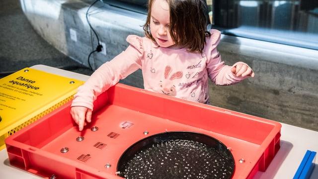 Ein kleines Mädchen drückt auf einen Knopf eines Ausstellungsexponates.