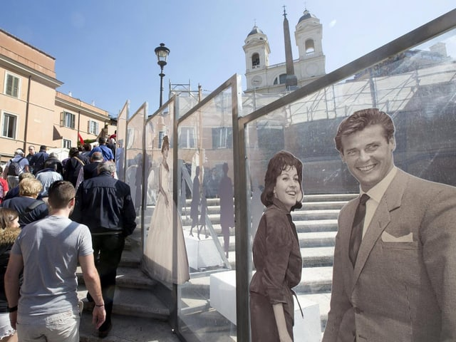 Touristen laufen an Glasplatten vorbei, auf denen Fotos von Stars angebracht sind.