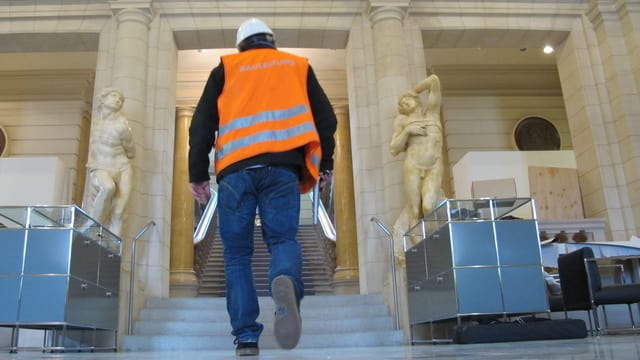 Bauarbeiter in Halle mit Statuen.