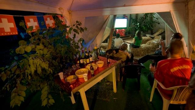 eine Handvoll Jugendliche verköstigen sich bei gedecktem Tisch, im Hintegrund wird ein Fussballspiel übertragen.