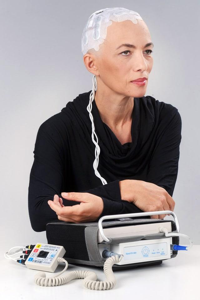 Beispielpatientin mit NovoTTF-100A und Elektroden am kahlgeschorenen Kopf.
