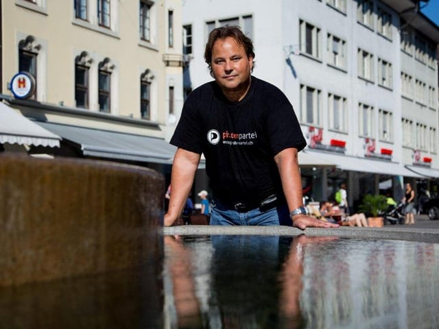 Ein Mann steht in der Winterthurer Altstadt. Im vordergrund ein Brunnen