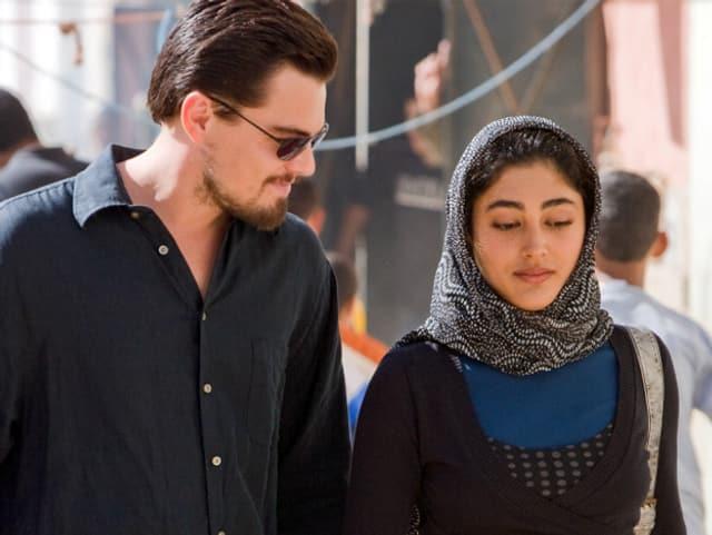 Ein Mann mit Sonnenbrille an der Seite einer Frau mit Kopftuch.