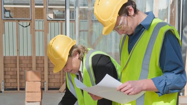 Eine Bauleiterin und ein Bauleiter beugen sich über Pläne