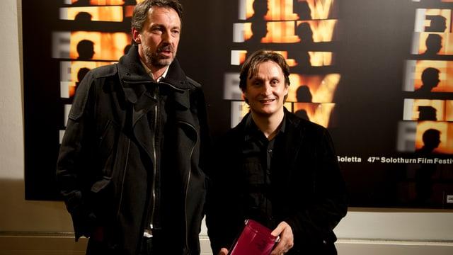 Zwei Männer. Einer zeigt einen Filmpreis, welcher