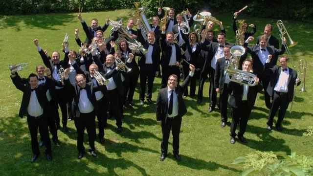 Musikanten und Musikantinnen einer Brass Band stehen mit ihren Instrumenten auf einer Wiese.