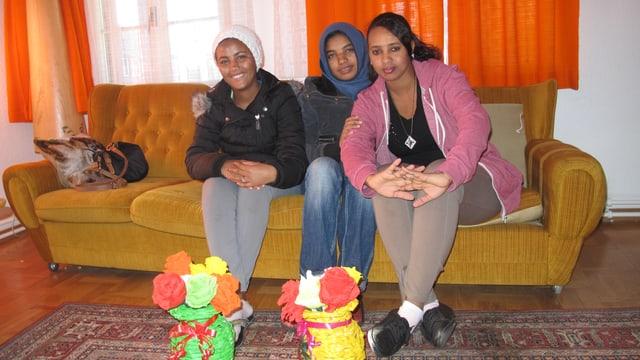 Drei Teenager-Mädchen auf einer Couch.