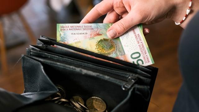 Hand steckt einen Geldschein in eine Geldbörse
