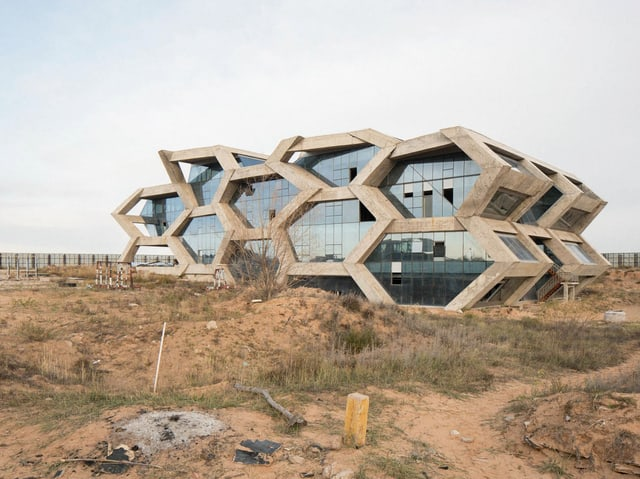 Ein futuristisches Gebäude, umgeben von Wüste.