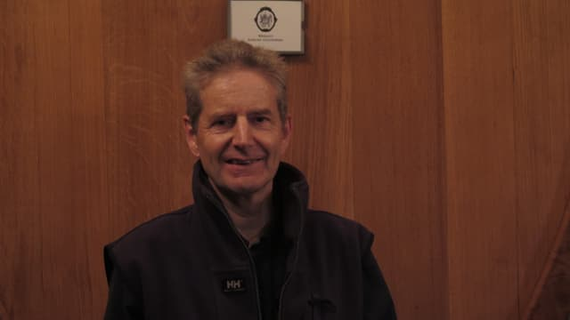 Mann mit kurzen grauen Haaren vor Weinfass