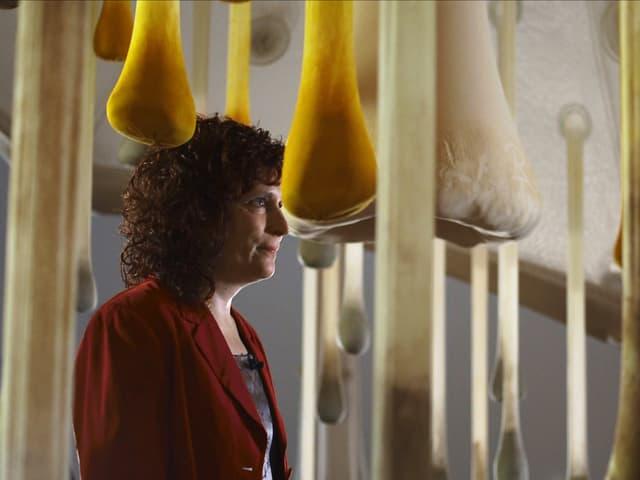Eine Frau steht inmitten von länglichen Gebilden aus Stoff, die in Tropfenform von der Decke hängen.