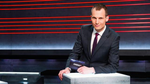 Arena-Moderator Jonas Projer vor Arena-Kulisse.