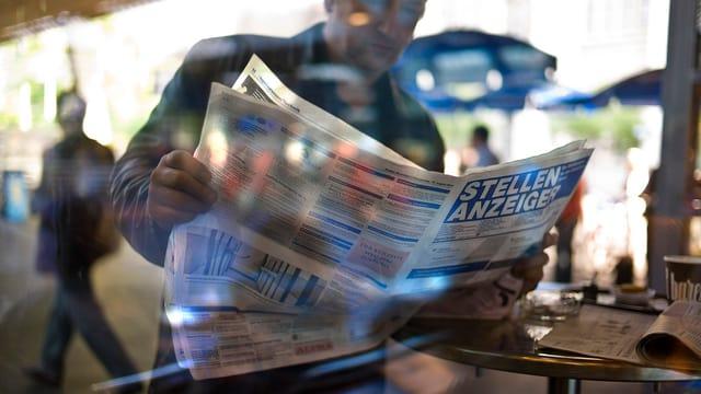 Mann liest Stellenanzeiger