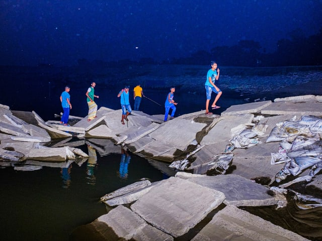 Menschen laufen auf Bergen von Müll, die im Wasser liegen, herum.